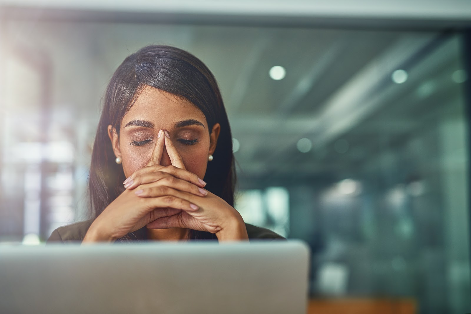 Shot of a young businesswoman looking stressed out while working in an office