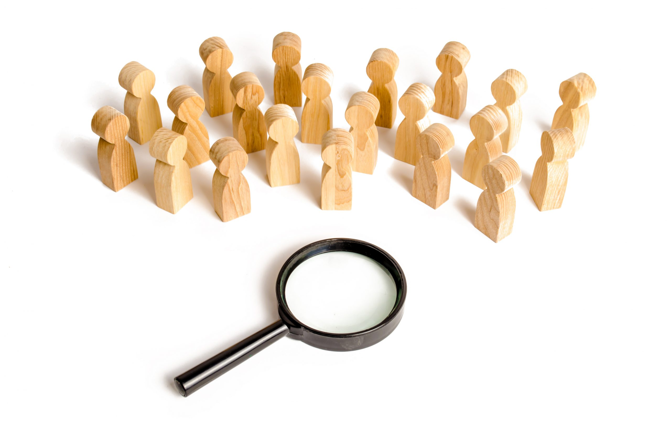 wooden figurines representing people in front of a magnifying glass