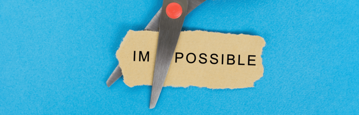 Scissors cutting the word impossible